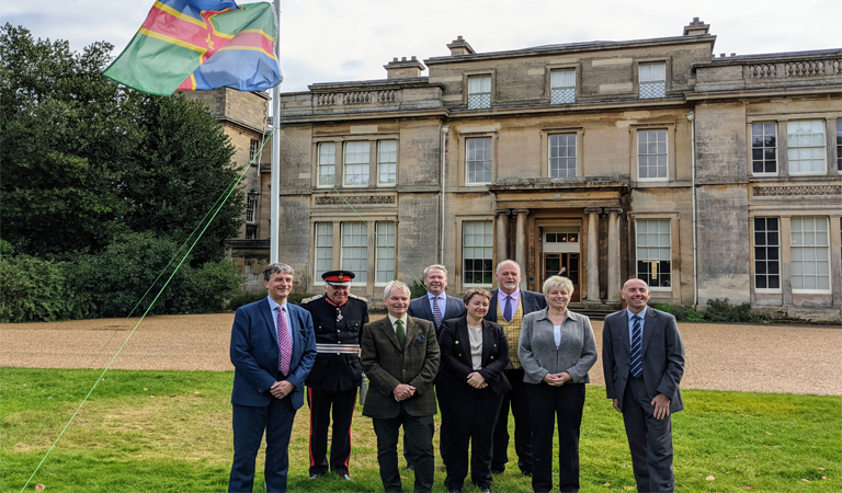 Photograph of Lincolnshire's Lord Lieutenant, MPs and council leaders flying the Lincolnshire flag at Normanby Hall