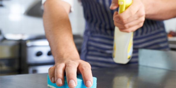 Photograph of a man cleaning down a kitchen counter after a service