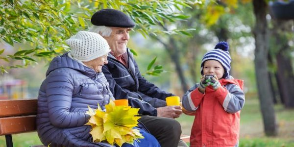 Senior couple and grandson drinking tea in autumn park