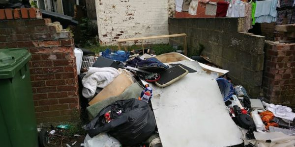 Dumped rubbish and debris in the back yard of a terraced house